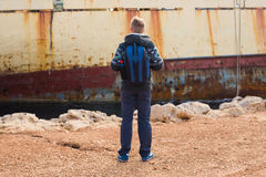 Male tourist looking at an abandoned ship on the sea or ocean back view. Adventure and tourism concept.  Stock Images