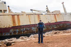 Male tourist looking at an abandoned ship on the sea or ocean back view. Adventure and tourism concept.  Stock Photos