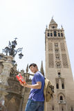 Male tourist looking at book by tower, low angle view Stock Photography