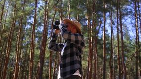 Male tourist looks through binoculars in the forest. Composition hiking, forester.