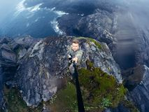 Male tourist man. Sitting jumping on a mountain on a sea background. Teriberka, Murmansk region, the Kola Peninsula, Russia. action cam royalty free stock images