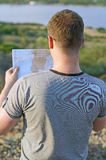 Male tourist with map. Male tourist with map on vacation. From the back Royalty Free Stock Photography