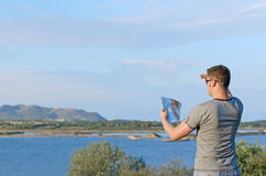 Male tourist with map. Male tourist with map on vacation. From the back Royalty Free Stock Images