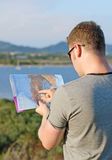 Male tourist with map. Male tourist with map on vacation. From the back Stock Image