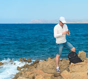 Male tourist with mobile phone. Male tourist with mobile phone standing near the sea Royalty Free Stock Photos
