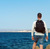 Male tourist near the sea. Male tourist with backpack standing near the sea. Place for your text Royalty Free Stock Images
