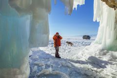 Male tourist photographer with dog near the ice grotto Olkhon Is Stock Images