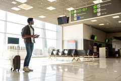 Male tourist preparing for flight. Serious young man is looking for right direction on information board at the airport. He is standing near his suitcase Stock Images