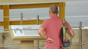 Male tourist reads information at open air museum, sightseeing tour on vacation. Stock footage stock video footage