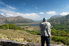 Male tourist, rear view taking pictures of Killarney National Pa Stock Photo