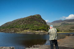 Male tourist, rear view taking pictures of Killarney National Park. Stock Photography