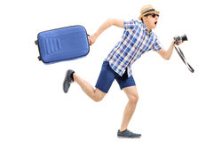 Male tourist rushing with his baggage and camera. In hand isolated on white background Stock Photo