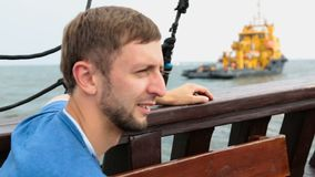 Male tourist sailing on pleasure boat past barge serving oil wells in sea. Stock footage stock footage
