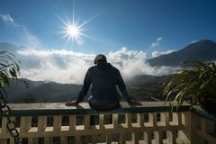 Male tourist sit on balcony seeing mountain landscape with low white clouds under brilliant sky. Ideas for travel and feeling.  Royalty Free Stock Image