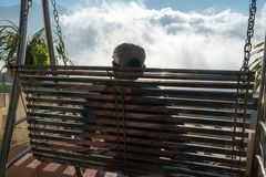 Male tourist sit on swing seeing mountain landscape with low white clouds under brilliant sky. Ideas for travel and feeling.  Royalty Free Stock Photo