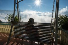 Male tourist sit on swing seeing mountain landscape with low white clouds under brilliant sky. Ideas for travel and feeling.  Royalty Free Stock Photography