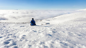 Male tourist sits on a hillside and looks at the Ukrainian Carpathians in the winter. Male tourist sits on a hillside and looks at the Ukrainian Carpathians in Royalty Free Stock Images