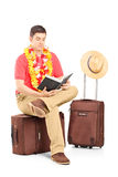 Male tourist sitting on a briefcase and reading a book Stock Images