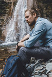 Male Tourist Sitting On The Rocks Near Waterfall, Side View. Hiking Destination Experience Lifestyle Concept. Young traveler man with a backpack, sits on the Royalty Free Stock Images