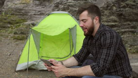 Male tourist sitting with a tablet near the tent. stock video footage