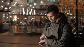 Male tourist with smartwatch on night street, looking away and touching watch. Male runner with smartwatch sitting in forest, looking away Royalty Free Stock Photo