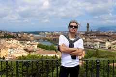Male tourist standing on balcony with Florence cityscape background, Italy. Man standing on balcony with Florence cityscape background. Concept of last minute Royalty Free Stock Photo