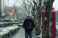 Male tourist standing on footpath on middle Huaihai road, Shangh. Ai in winter during snow Royalty Free Stock Photo