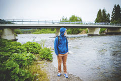 Male tourist standing beside the mountain river.  Royalty Free Stock Image
