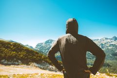 Male tourist standing in mountain scenery. And looking at beautiful landscape on sunny summer day Royalty Free Stock Photography