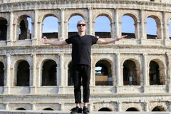 Male tourist standing near Coloseum in background in Rome, Italy. Male tourist wearing black clothes and standing near Coloseum in background in Rome, Italy Royalty Free Stock Photo