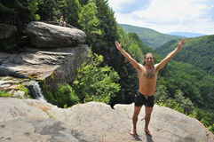 A male tourist stands on a boulder ridge. Overlooking a portion of panorama. View from ledge on top of Kaaterskills waterfall in the Catskills Mountains of New Royalty Free Stock Image