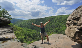A male tourist stands on a boulder ridge. Overlooking a portion of panorama. View from ledge on top of Kaaterskills waterfall in the Catskills Mountains of New Royalty Free Stock Photo