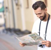 Handsome tourist on the street looking at a guide. Male  tourist on the street looking at a guide Stock Photos