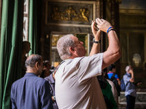 Male tourist takes smartphone photo in Palace of Versailles, Fra Stock Photography