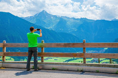 Male tourist taking photo of alpine landscape. Young tourist taking a photo of alpine landscape, green slopes and high mountain peaks, Austria, Alps Royalty Free Stock Image