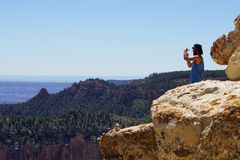 Male tourist taking a photo from Bright Angel Point, South rim, Grand Canyon focus on pinnacle. Royalty Free Stock Images