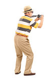 Male tourist taking a photo with camera. Isolated on white background, rear view Royalty Free Stock Photos