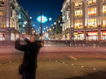Male tourist taking photos at London Oxford Circus at night at C Stock Image