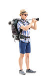 Male tourist taking picture with a camera. Full length portrait of a male tourist taking a picture with a camera isolated on white background Stock Photo