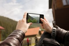 Male tourist taking picture in the mountains of the Carpathians. On his smartphone Stock Image