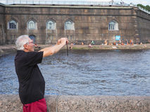 Male tourist taking pictures of the sights and makes a selfie in the summer. Saint-Petersburg. Peter and Paul fortress. The summer Stock Image