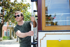 Male tourist taking a ride in famous cable car in San Francisco. Male cheerful tourist taking a ride in famous cable car in San Francisco, California, USA Royalty Free Stock Photo