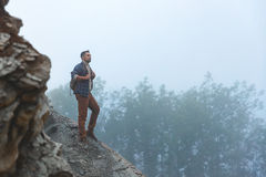 Male tourist on top of mountain in fog in autumn. Male tourist on top of gray mountain in fog in autumn Stock Image