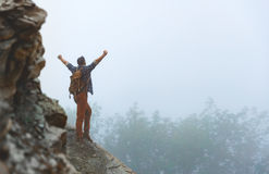 Male tourist on top of mountain in fog in autumn. Male tourist on top of gray mountain in fog in autumn Stock Photo