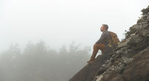 Male tourist on top of mountain in fog in autumn. Male tourist on top of gray mountain in fog in autumn Royalty Free Stock Photography