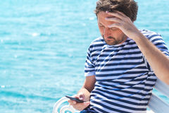 Male tourist using mobile phone at seaside on summer holiday. Male tourist in stripped shirt using mobile phone for communication at seaside on summer holiday Royalty Free Stock Photography