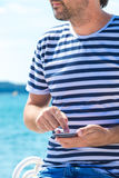 Male tourist using mobile phone at seaside on summer holiday. Male tourist in stripped shirt using mobile phone for communication at seaside on summer holiday Royalty Free Stock Image