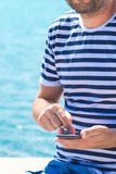 Male tourist using mobile phone at seaside on summer holiday. Male tourist in stripped shirt using mobile phone for communication at seaside on summer holiday Stock Photo
