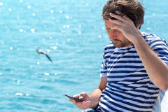 Male tourist using mobile phone at seaside on summer holiday. Male tourist in stripped shirt using mobile phone for communication at seaside on summer holiday Royalty Free Stock Photos