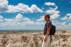 Male tourist viewing South Dakota badlands. Male tourist overlooking South Dakota badlands against blue sky Stock Images